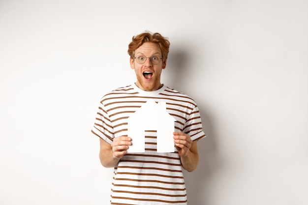 Glücklicher und überraschter rothaariger mann, der haus gewinnt, papierhausmodell hält und kamera anstarrt, freudig über weißem hintergrund stehend.