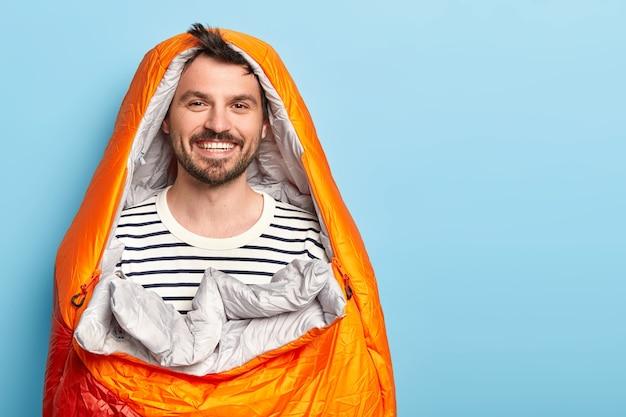 Glücklicher unrasierter mann urlauber verbringt urlaub in der nähe von bergen auf dem campingplatz, schläft im schlafsack, lächelt positiv, trägt einen gestreiften pullover und posiert an der blauen wand