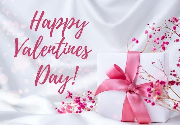 Glücklicher valentinstag, der grußkarte beschriftet. geschenkbox mit trockenen rosa blumen des rosa bandes. helles pastellkonzept.