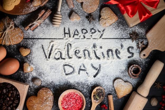 Glücklicher valentinstag geschrieben auf mehl. lebkuchen herzförmige kekse, gewürze, kaffeebohnen und backzubehör