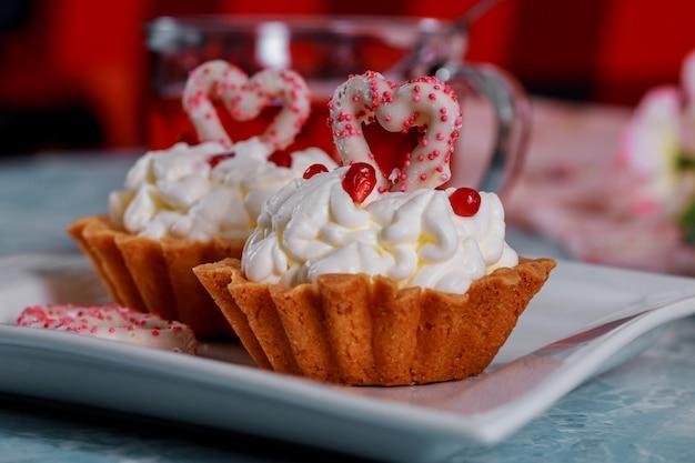 Glücklicher valentinstag wird auf dekorative kleine kuchen mit valentinstagkonzept geschrieben