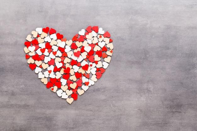 Glücklicher valentinstaghintergrund. mit kleinen herzen auf grauem hintergrund.