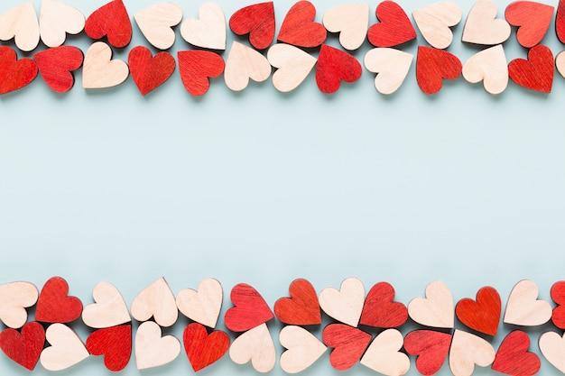 Glücklicher valentinstaghintergrund. rote herzen auf weißem hölzernem hintergrund.