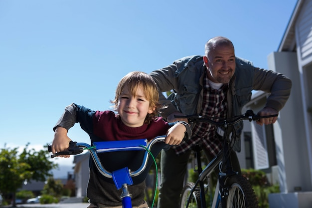 Glücklicher vater auf einem fahrrad mit seinem sohn an einem sonnigen tag