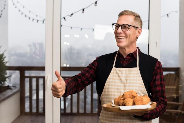 Glücklicher vater, der daumen beim halten der platte der muffins aufgibt