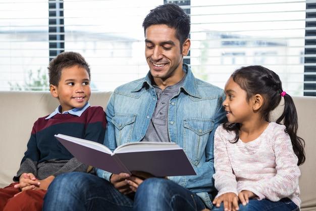 Glücklicher vater, der ein buch für seine kinder liest