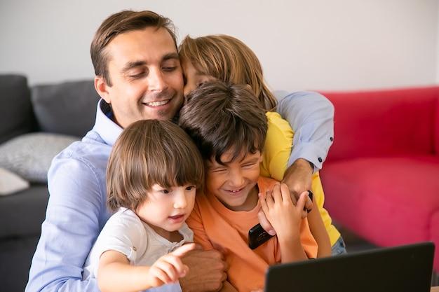 Glücklicher vater, der mit niedlichen kindern umarmt. kaukasischer vater mittleren alters, der im wohnzimmer sitzt, niedliche kinder umarmt, handy hält und lächelt. vaterschafts-, kindheits- und familienkonzept