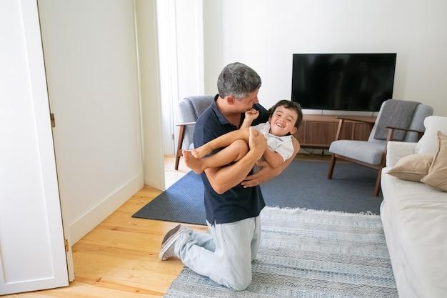 Glücklicher vater, der seinen sohn in den händen hält und auf knien im wohnzimmer steht.
