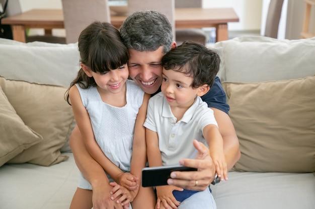 Glücklicher vater, der zwei kinder auf schoß hält, selfie nimmt oder telefon für videoanruf verwendet