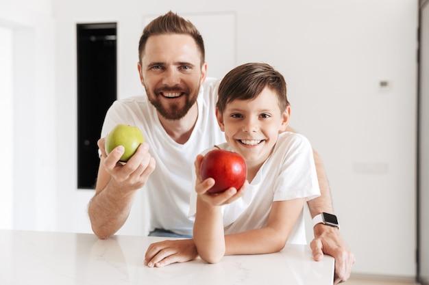 Glücklicher vater des jungen mannes vater hält äpfel mit sohn