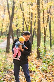 Glücklicher vater hält die kleine tochter in ihren armen zwischen den bäumen, vaterschaft, glücklich, familie, spaziergang