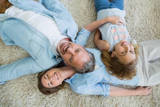 Glücklicher vater mit seinem sohn und seiner tochter, die auf teppich liegen