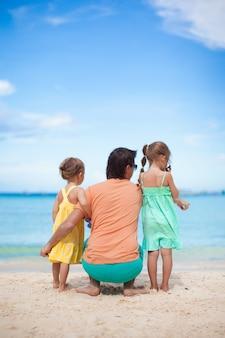 Glücklicher vater mit seinen zwei töchtern, die auf tropischen strandferien sitzen
