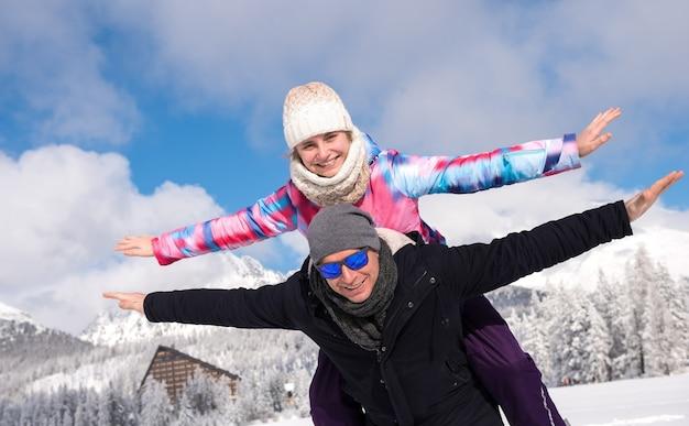 Glücklicher vater mit tochter, die winterferien über bergen genießen