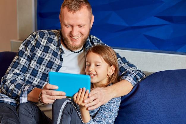 Glücklicher vater mit tochter mit tablet-computer im wohnzimmer, auf dem sofa zu hause, beim lesen oder spielen vom tablet. glückliche familie.