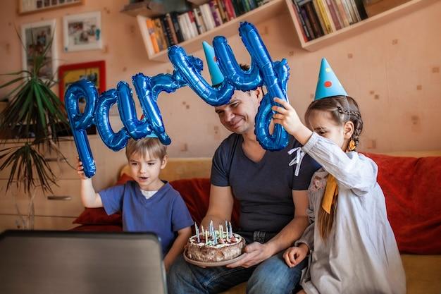 Glücklicher vater mit zwei geschwistern, die geburtstag über internet in quarantänezeit feiern, selbstisolation