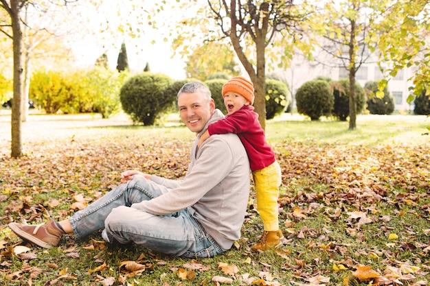 Glücklicher vater spielt mit seiner kleinen tochter im park am herbstlaub und hebt sie hoch in seine arme