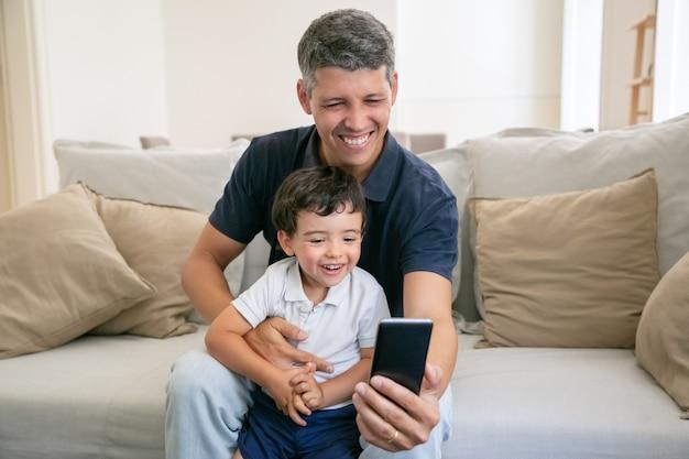 Glücklicher vater und entzückender kleiner sohn, der spaß zusammen hat, telefon für video-chat verwendend, während zu hause auf der couch sitzend