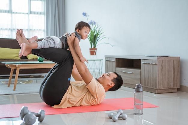 Glücklicher vater und kind, die übung zusammen machen. porträt des gesunden familientrainings zu hause. mann und sein sohn sport