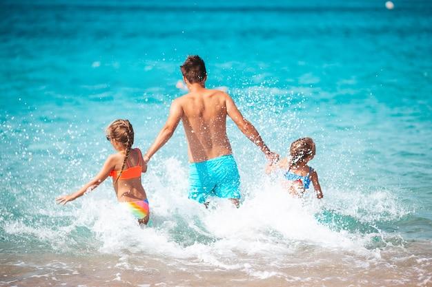 Glücklicher vater und kleine töchter im strandurlaub spielen im seichten wasser