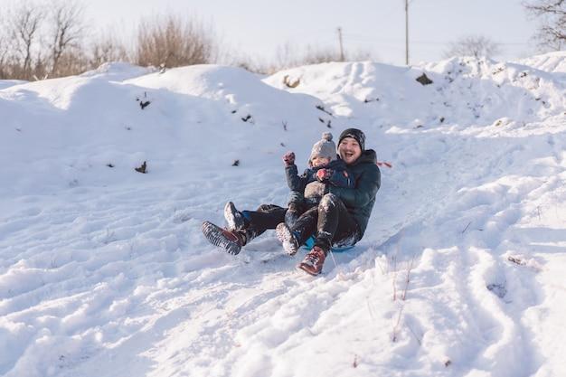 Glücklicher vater und kleiner junge spielen mit schneeschlitten