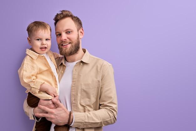 Glücklicher vater und kleiner sohn, die an der kamera lächelnd, jungen kaukasischen familienvater und sohn in der freizeitkleidung lokalisiert auf lila hintergrund aufwerfen