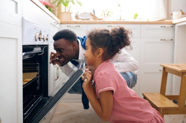 Glücklicher vater und kleines kind kochen kuchen im ofen beim frühstück. lächelnde familie in der küche morgens. papa füttert weibliches kind, gute beziehung