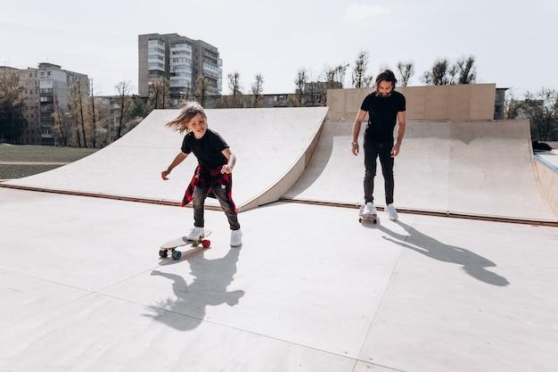 Glücklicher vater und sein kleiner sohn in freizeitkleidung fahren skateboards in einem skatepark mit rutschen am sonnigen tag.