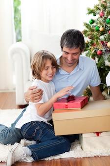 Glücklicher vater und sein sohn, die weihnachtsgeschenke halten