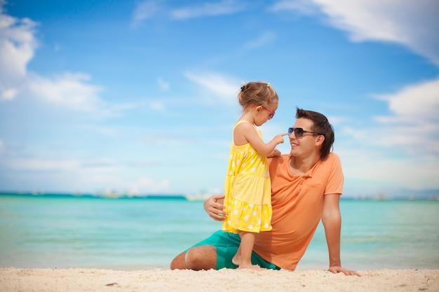 Glücklicher vater und seine entzückende kleine tochter am strand
