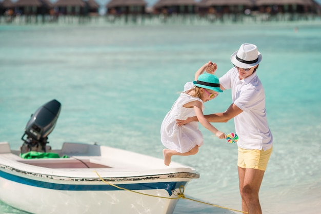 Glücklicher vater und seine entzückende kleine tochter am tropischen strand, der spaß hat