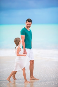 Glücklicher vater und seine entzückende kleine tochter am tropischen strand zusammen gehend