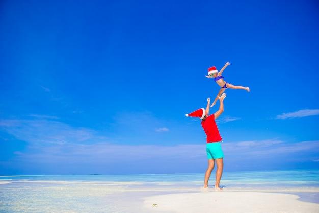 Glücklicher vater und seine entzückende kleine tochter in santa hat am tropischen strand