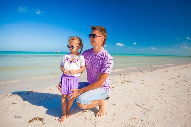 Glücklicher vater und seine entzückende kleine tochter zusammen am strand