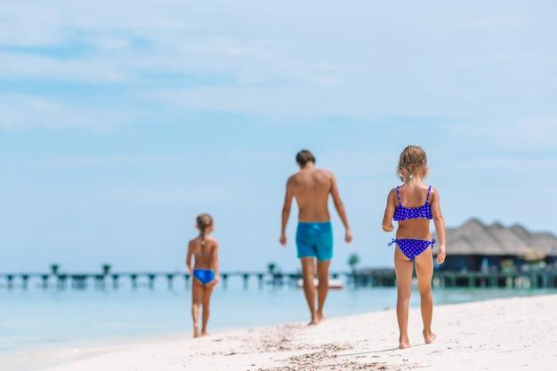 Glücklicher vater und seine entzückenden kleinen töchter am tropischen strand, der spaß hat