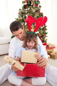 Glücklicher vater und seine tochter, die weihnachtsgeschenke öffnen