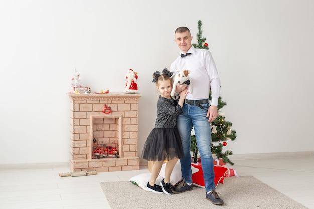 Glücklicher vater und seine tochter zu hause mit weihnachtsbaum