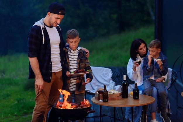 Glücklicher vater und sohn bereiten einen grill auf einem familienurlaub vor