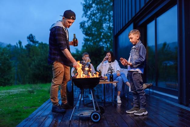 Glücklicher vater und sohn bereiten einen grill während eines familienurlaubs auf der terrasse ihres modernen stilvollen hauses vor
