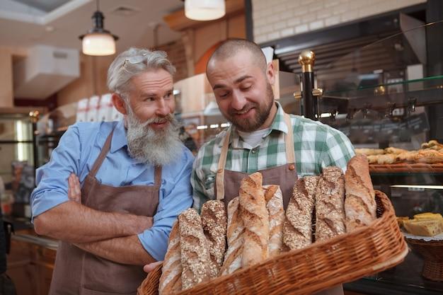 Glücklicher vater und sohn, die köstliches frisch gebackenes brot in ihrer familienbäckerei verkaufen