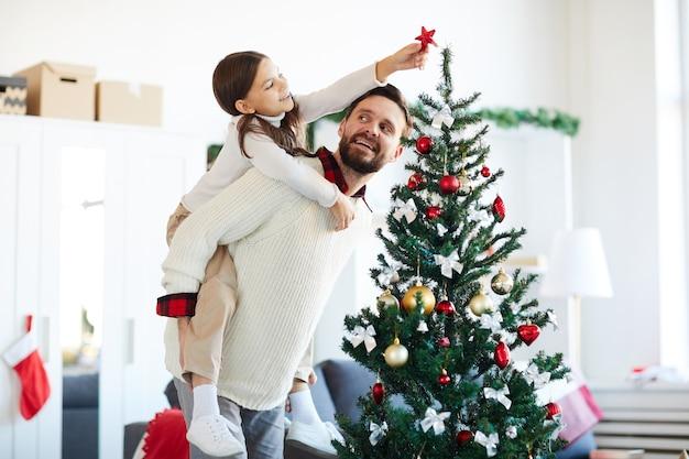 Glücklicher vater und tochter, die den weihnachtsbaum schmücken