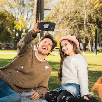 Glücklicher vater und tochter, die selfie mit handy nimmt