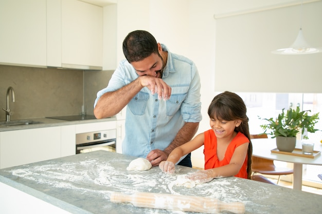 Glücklicher vater und tochter, die spaß haben, während teig auf küchentisch kneten. vater bringt seinem mädchen bei, brot oder kuchen zu backen. familienkochkonzept