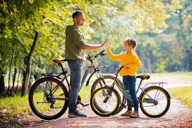 Glücklicher vater und tochter gehen an einem sonnigen tag mit fahrrädern im herbstpark spazieren.