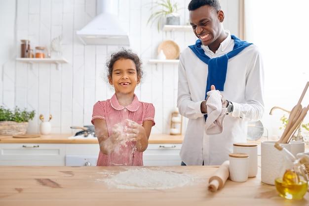 Glücklicher vater und tochter kochen kuchen zum frühstück. lächelnde familie isst morgens in der küche. papa füttert weibliches kind, gute beziehung