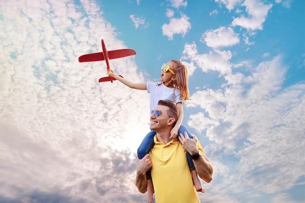 Glücklicher vater und tochter spielen mit flugzeug