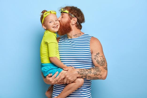 Glücklicher vater und tochter tragen schutzbrille und sommerkleidung, haben gemeinsam spaß in der ruhe. der liebevolle vater trägt ein kleines mädchen, küsst sie auf die wange und drückt die liebe aus. familien- und erholungskonzept