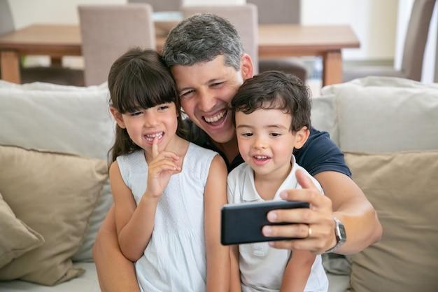 Glücklicher vater und zwei kinder, die selfie nehmen oder telefon für videoanruf verwenden, während sie zusammen auf sofa zu hause sitzen.