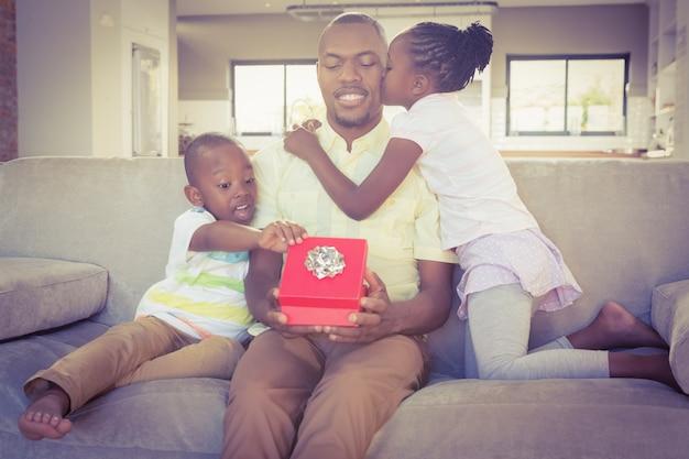 Glücklicher vater wird von seinen zwei kindern geküsst
