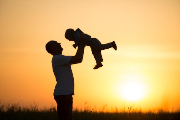 Glücklicher vater wirft das baby bei sonnenuntergang
